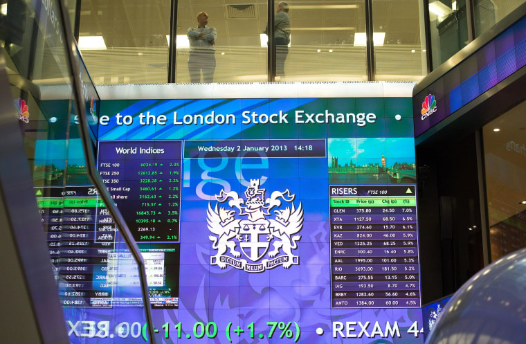 Workers speak above an electronic information board at the London Stock Exchange in the City of London on Jan. 2, 2013.