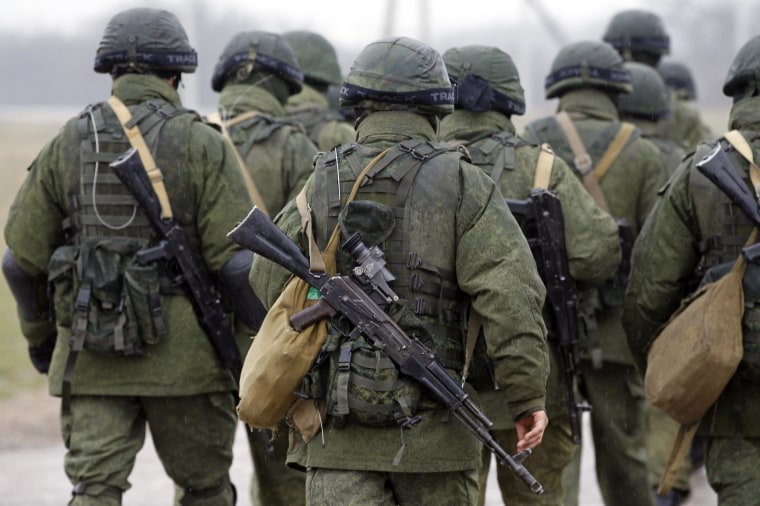 Uniformed men, believed to be Russian servicemen, walk in formation near a Ukrainian military base in the village of Perevalnoye outside Simferopol