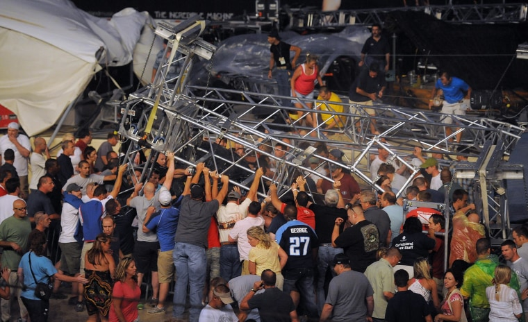 Fans at a Sugarland concert attempt to hold up the stage after high winds blew the stage over at the Indiana State Fair Grandstands, Saturday, Aug. 13, 2011, in Indianapolis. (AP Photo/The Indianapolis Star, Matt Kryger)