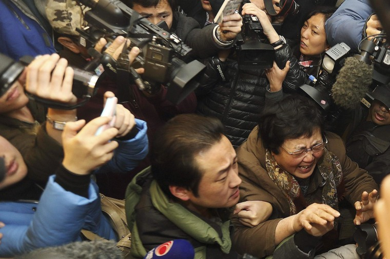 Image: A relative of a passenger of Malaysia Airlines flight MH370 cries as she walks past journalists at a hotel in Beijing