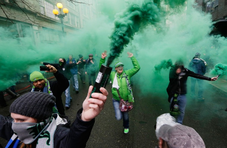 """Image: Members of the Emerald City Supporters and other fan groups burn smoke devices as they take part in the traditional """"March to the Match"""" before the Seattle Sounders season-opening MLS soccer match"""