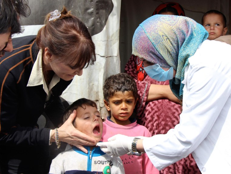 Dr. Nancy Snyderman assists another doctor in checking on Yusef at a Syrian refugee camp in Lebanon.