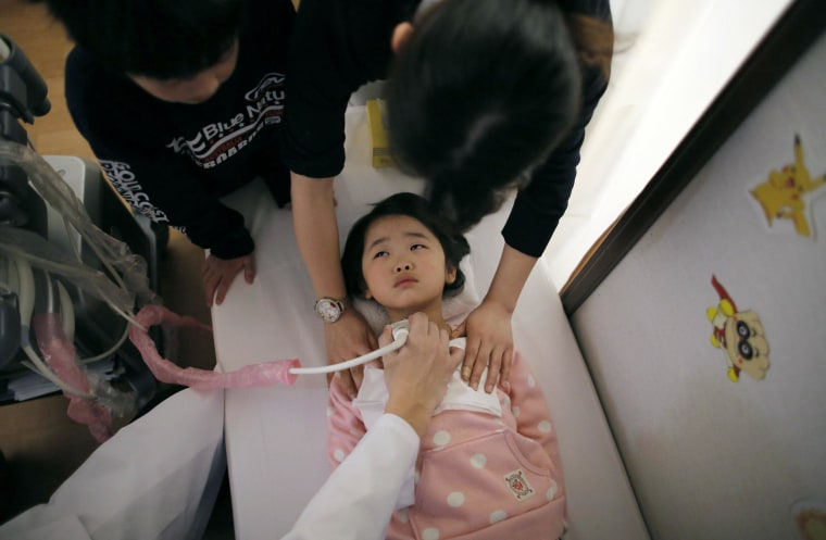 A doctor conducts a thyroid examination on five-year-old girl as her older brother and a nurse take care of her at a clinic in temporary housing complex in Nihonmatsu, west of the tsunami-crippled Fukushima Daiichi nuclear power plant, Fukushima prefecture.