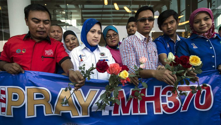 People hold roses and a banner as they pray for missing flight MH370 at a hotel in Putrajaya, Malaysia.