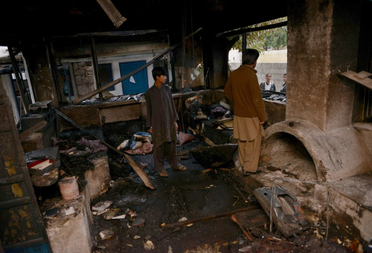 Image: Pakistani yoga center workers are pictured in the charred interior of their premises