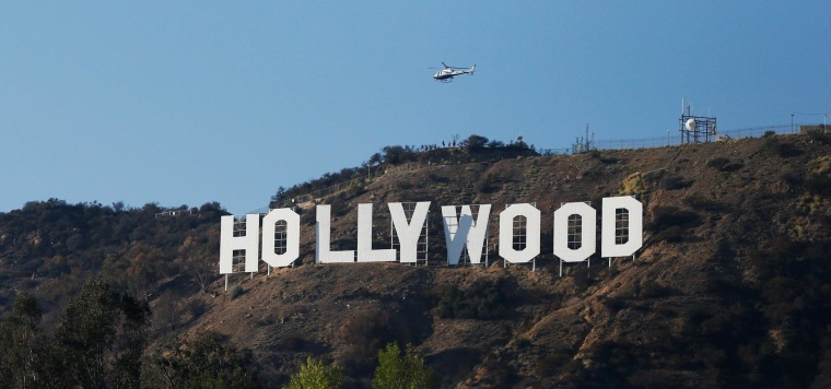Image: A LAPD helicopter flies over the Hollywood sign in Hollywood
