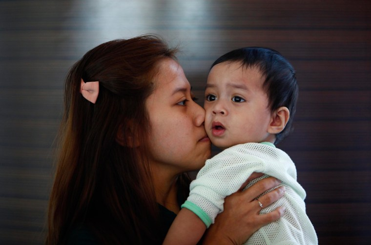 Image: Erny Khairul, whose husband Mohd Khairul Amri Selamat was onboard the missing Malaysia Airlines flight MH370, kisses her daughter inside a hotel they are staying at in Putrajaya