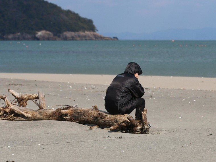 SHICHIGAHAMA TOWN, JAPAN - MARCH 11: A man sits on a log before observing a moment of silence at 2:46 p.m., the time at which the magnitude 9.0 earthquake struck at Shobuta beach on March 11, 2014 in Shichigahama town, Miyagi Prefecture, Japan. On March 11 Japan commemorates the third anniversary of the magnitude 9.0 earthquake and tsunami that claimed more than 18,000 lives, and subsequent nuclear disaster at the Fukushima Daiichi Nuclear Power Plant.  (Photo by Yuriko Nakao/Getty Images)