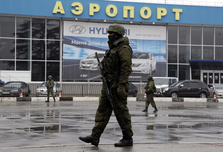 Image: Unidentified armed men patrolling outside Simferopol airport