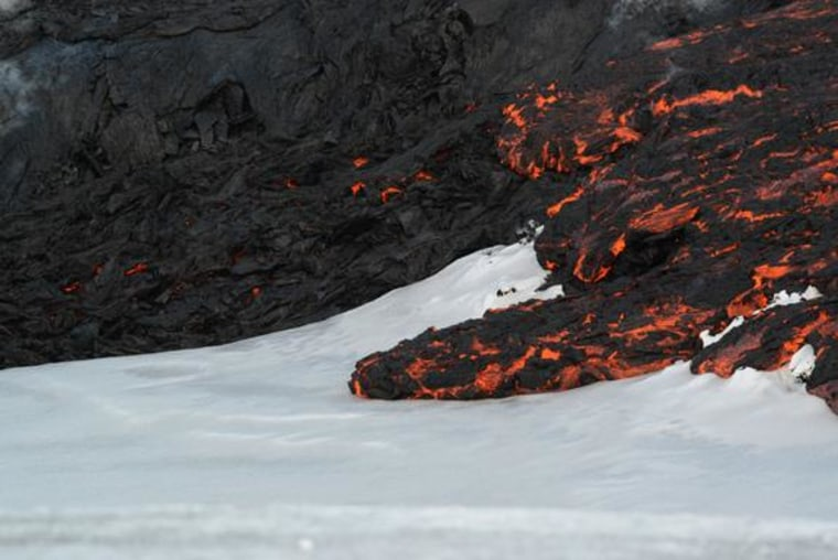 Image: Lava flows on top of snow at Tolbachik volcano in Russia in April 2013.