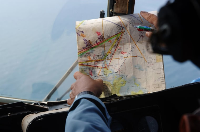 This picture taken aboard a Vietnamese Air Force Russian-made MI-171 helicopter shows a crew member checking a map during a search flight some 200 km over the southern Vietnamese waters off Vietnam's island Phu Quoc on March 11, 2014 as part of continued efforts aimed at finding traces of the missing Malaysia Airlines MH370. Malaysian police said on March 11 one of two suspect passengers who boarded a missing passenger jet was an Iranian illegal immigrant, as relatives of some of the 239 people on board said they were losing hope for a miracle.