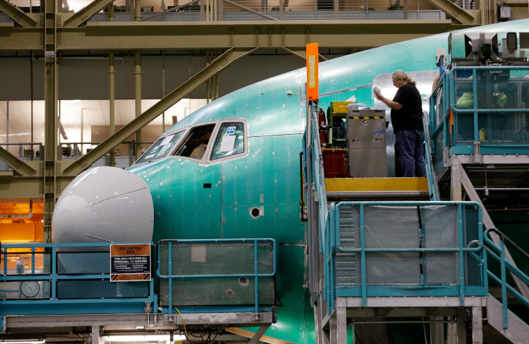 A worker stands near the front of a Boeing 777 jet under construction