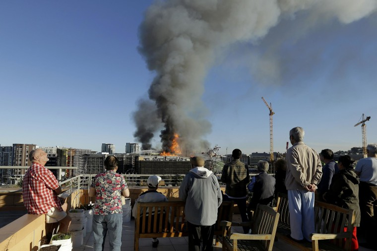 Image: Residents at Mission Creek Senior Community building look from their roof at a fire burning in San Francisco