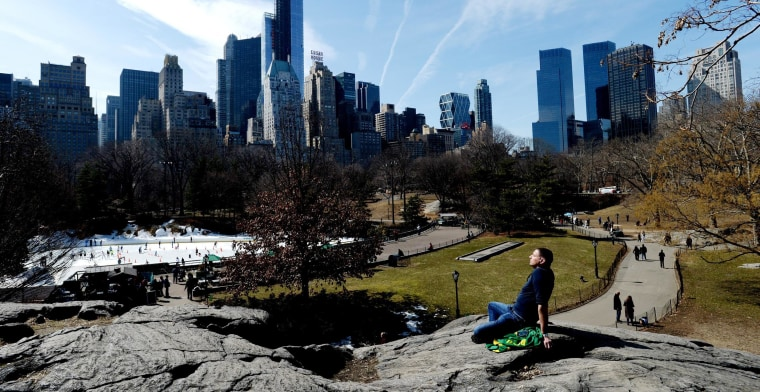 Roberto Serrano, of New York, sunbathes while sitting in Central Park in New York City on March 11, 2014.