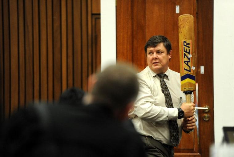 Image: Police forensic expert Col. Johannes Vermeulen holds cricket bat while standing next to Oscar Pistorius' door