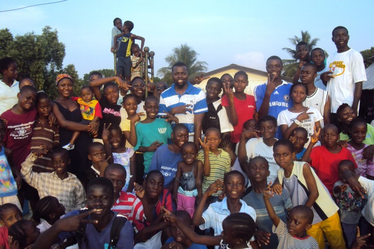Image: Saye-Maye Cole today, center, in white-and-blue shirt, with children at an SOS Children's Village in Liberia