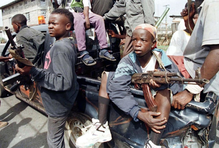 Image: Two child soldiers on an NPFL militia vehicle ride through the streets of Monrovia, Liberia