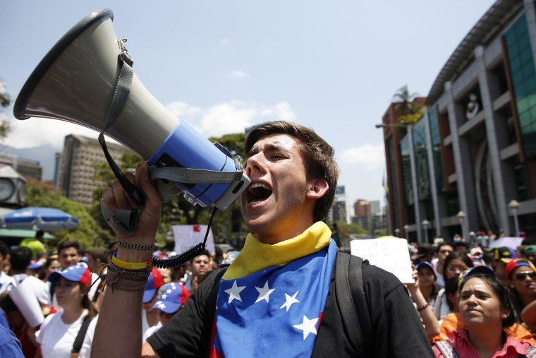 Image: An anti-government protester shouts into a loudhailer during a demonstration in Caracas