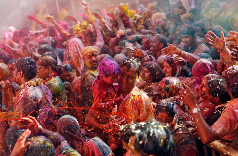 Image: Hindu devotees react as priests throw coloured water on them during Holi celebrations at the Bankey Bihari temple in Vrindavan