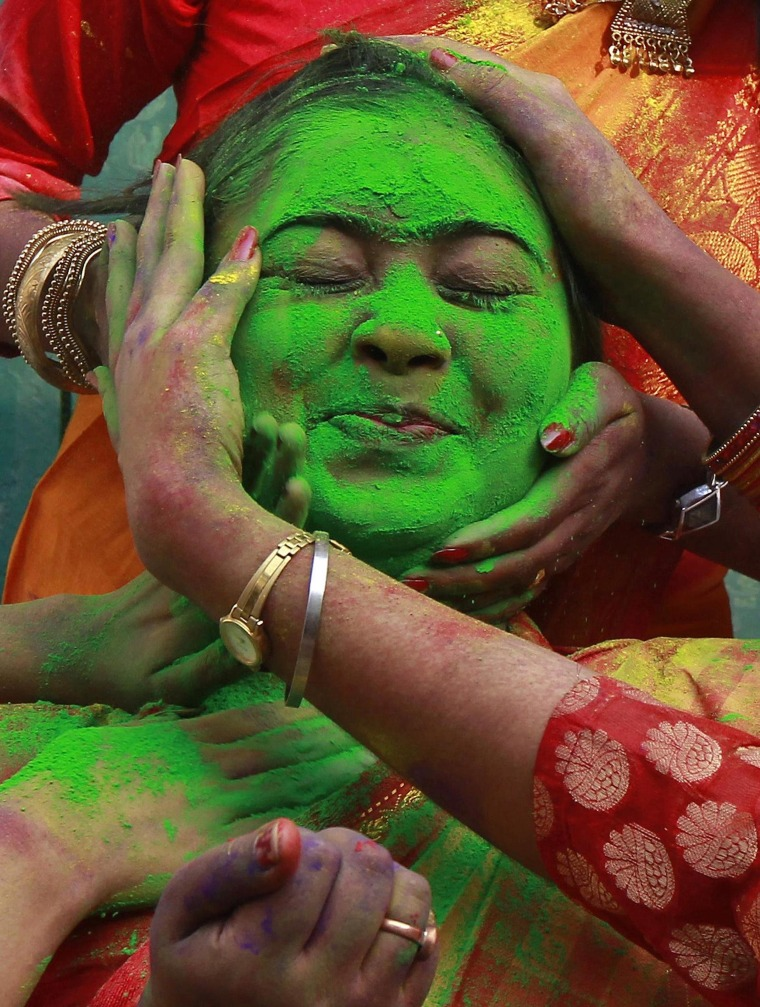 Image: A student of Rabindra Bharati University reacts as her fellow students apply coloured powder to face during celebrations for Holi in Kolkata