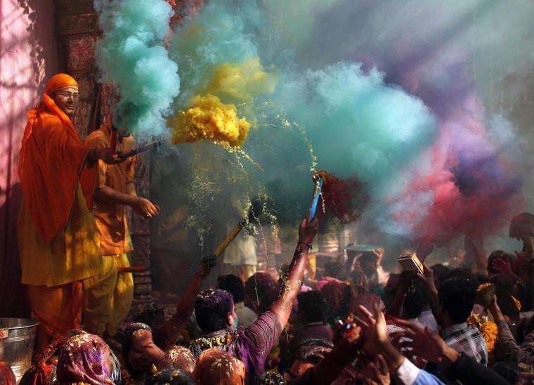Image: Hindu priests throws coloured powder at the devotees during Holi celebrations at Bankey Bihari temple in Vrindavan