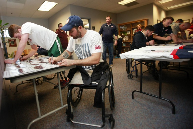 Image: 2014 U.S. Paralympic sled hockey team signs autographs
