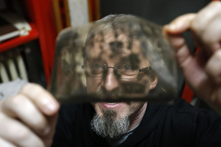 """Image: Photo enthusiast Cezar Popescu looks at a negative from the """"Costica Acsinte picture archive"""" at Ialomita county museum in Slobozia"""