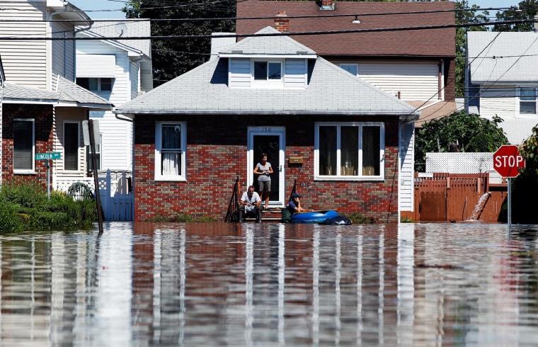 Image: Residents wait for flooding to subside in the town of Totowa, N.J.
