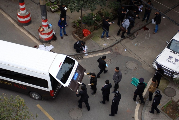 Image: Police and investigators inspect the crime scene where attackers armed with knives killed three people in Changsha