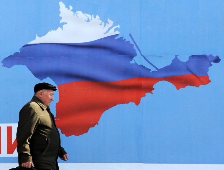 Image: A man walks past a poster in Sevastopol