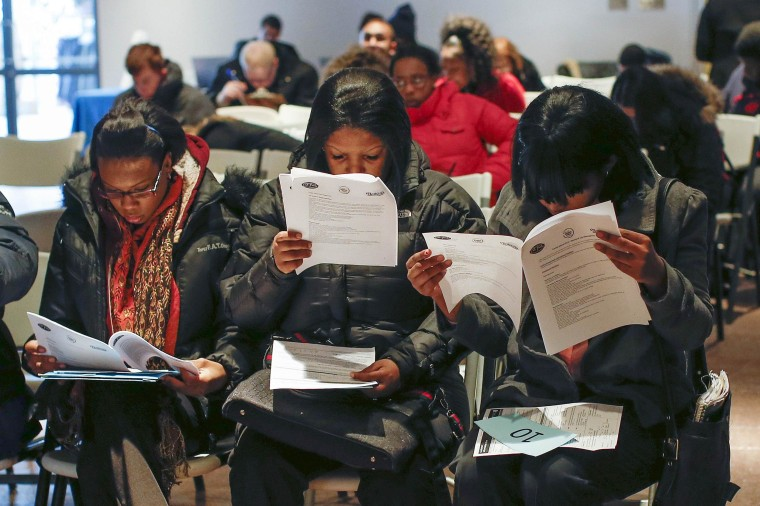 Image: People fill out application forms before a screening session for seasonal jobs at Coney Island in New York