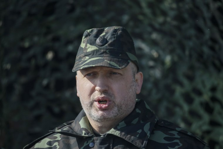 Image: Ukraine's acting President Turchinov speaks with the media during a military exercise near the village of Goncharivske