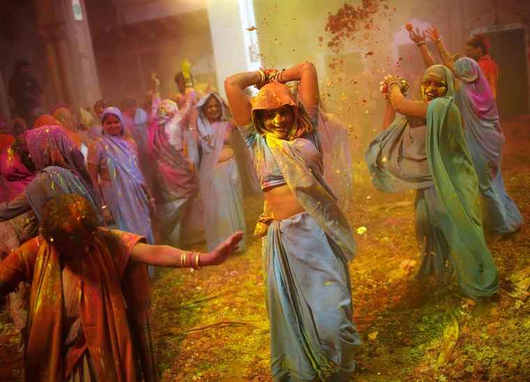 Image: Women, who are widows, dance during the Holi celebrations at a widow's ashram in Vrindavan