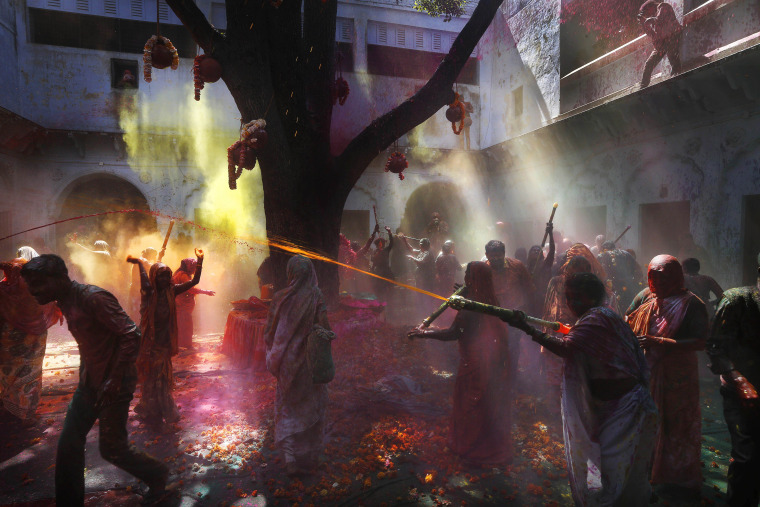 Image: Indian Hindu widows and Harijan, or former untouchable, women play with colored water for the first time as part of Holi celebrations