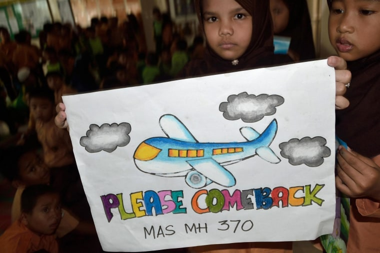 Image:An Indonesian student displays a message expressing prayers