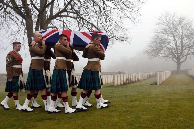 Image: Soldiers carry the flag-draped casket of British soldier William McAleer