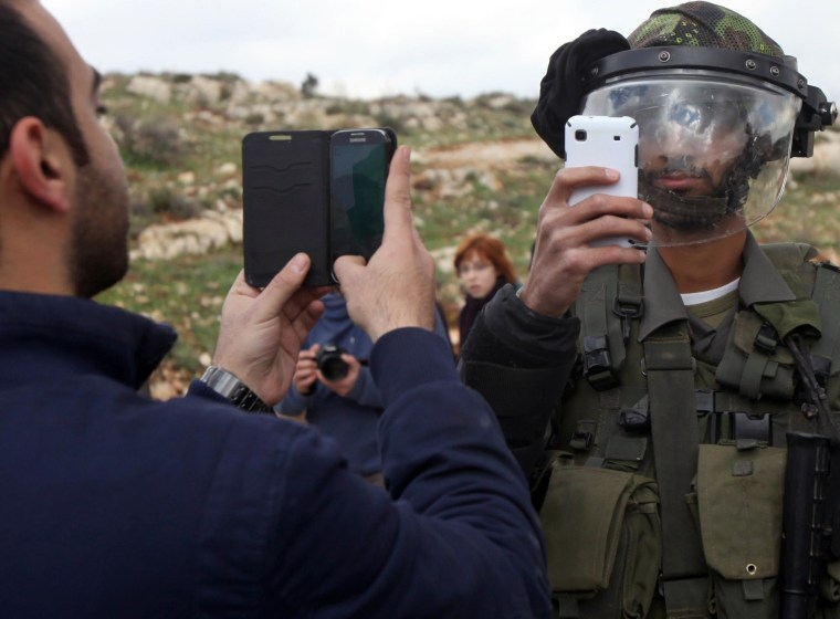 Image: A Palestinian man and a member of the Israeli security forces take pictures of each other with their mobile phones
