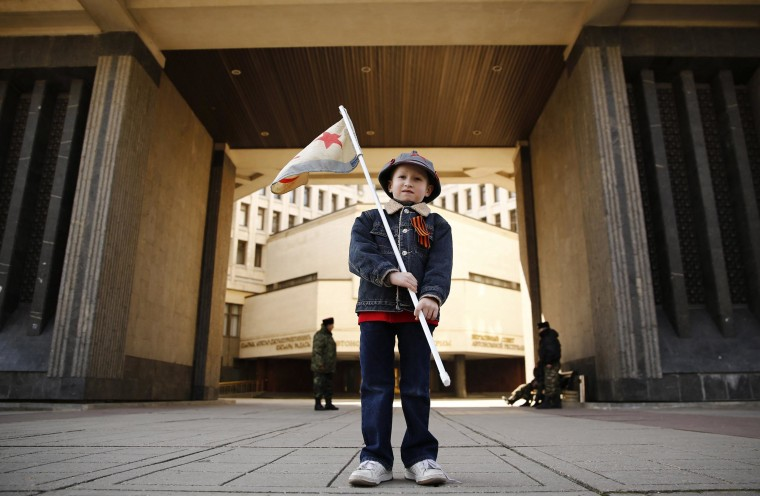 Image: A boy stands in front of the Crimean parliament building, with members of Crimean self-defence units seen in the background, on the eve of a referendum in Simferopol