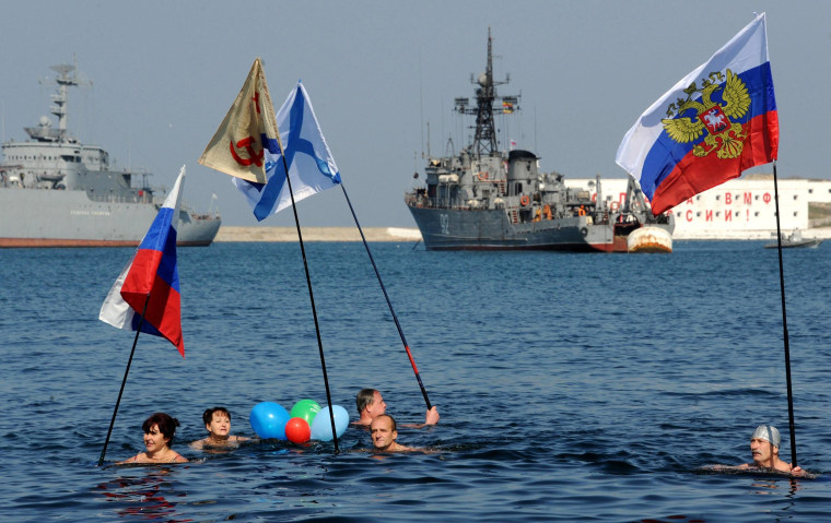 Image: People swimming in the cold waters of the harbor of Sevastopol hold Russian national and navy flags