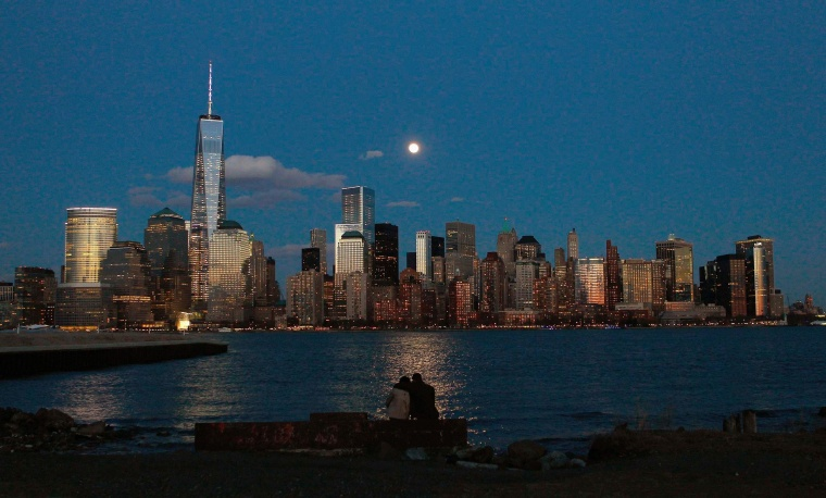 Image: The moon rises behind the skyline of New York's Lower Manhattan as two people watch from a park along the Hudson River in New Jersey