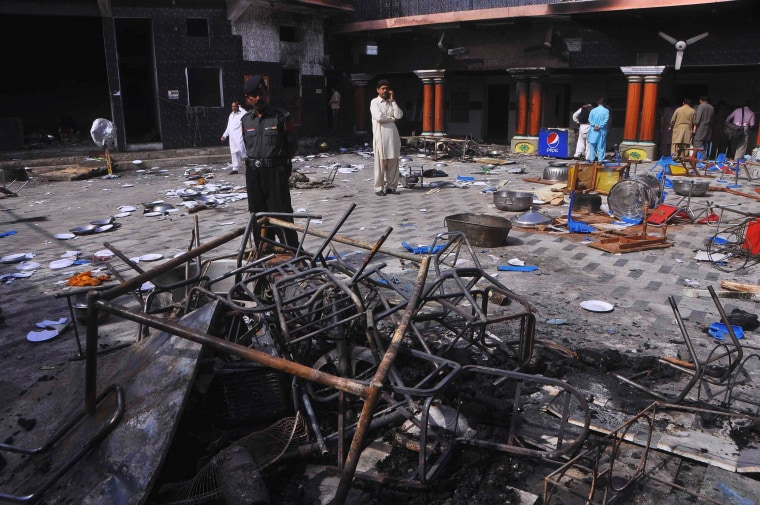 Image: A security official and members of the Hindu community stand inside a temple that was attacked on Saturday night, in Larkana