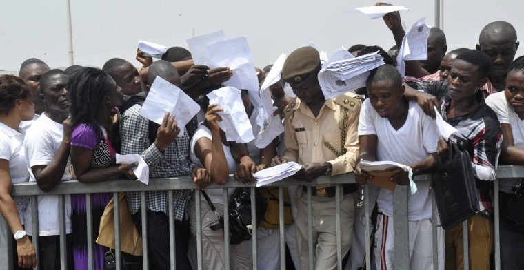 Image: Applicants struggle to submit copies of their acknowledgement forms to an immigration officer during a recruitment drive for the Nigeria Immigration Service at the National Stadium in Abuja