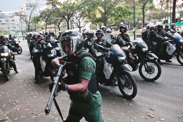 Image: A Bolivarian National Guard aims his weapon in search of anti-government demonstrators