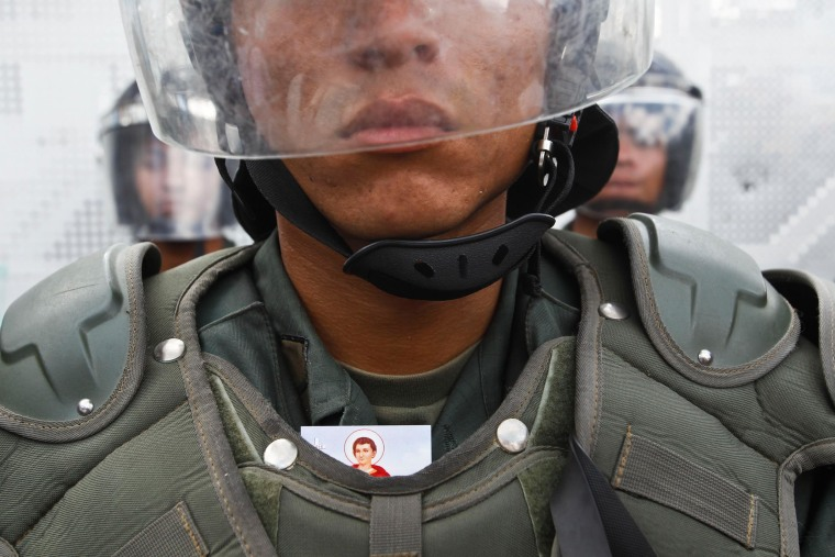 Image: A religious image is tucked behind body armor