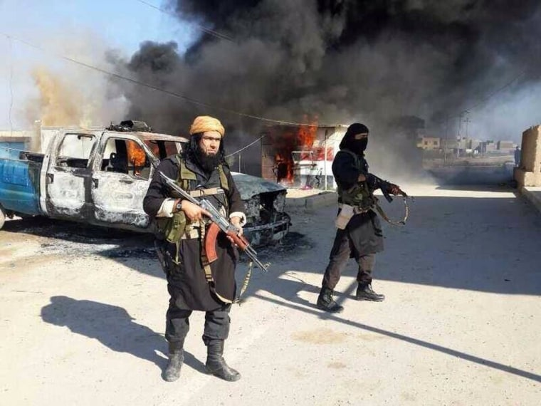 This undated image posted on a militant website on Jan. 4, 2014, shows Shakir Waheib, a senior member of the al Qaeda-linked Islamic State of Iraq and the Levant (ISIL), left, next to a burning police vehicle in Iraq's Anbar province.