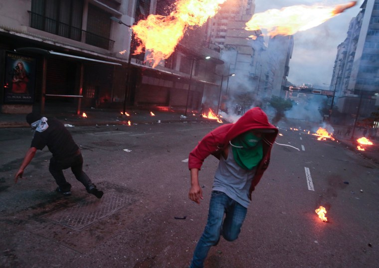 Image: Protesters take cover after launching Molotov cocktails