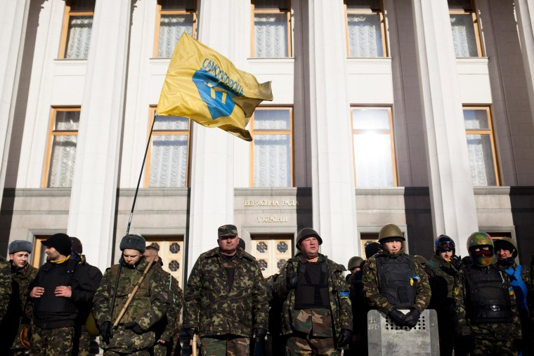 Image: Men in military fatigues outside Kiev's parliament