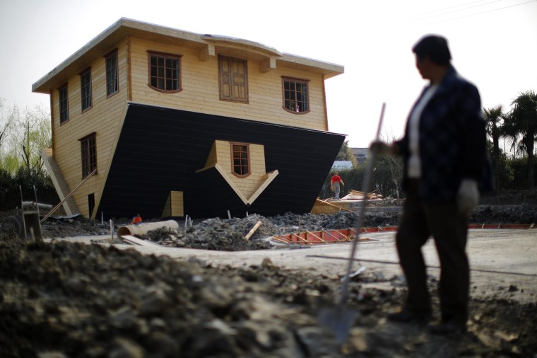 Image: A laborer takes a break as she works at an upside-down house under construction