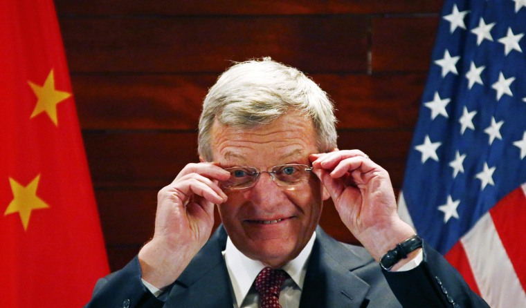 Image: U.S. Ambassador to China Baucus adjusts his glasses in front of Chinese and American national flags during a news conference at the U.S. Embassy, upon his arrival to his new post, in Beijing