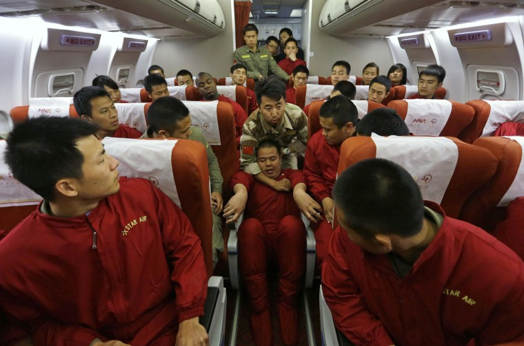 Image: An instructor holds a student by his neck during a special course on flight safety on the outskirts of Beijing